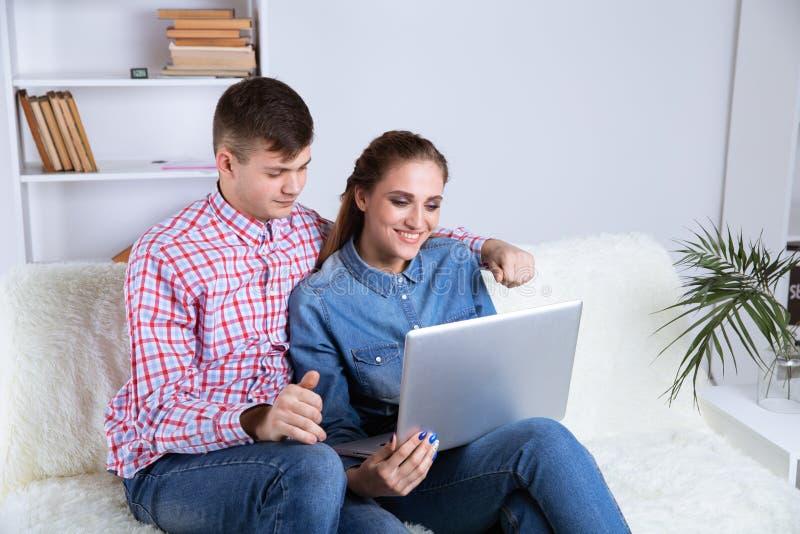 Par av den unga mannen och kvinnan direktanslutet i internet som hemma sitter på en soffa royaltyfri bild
