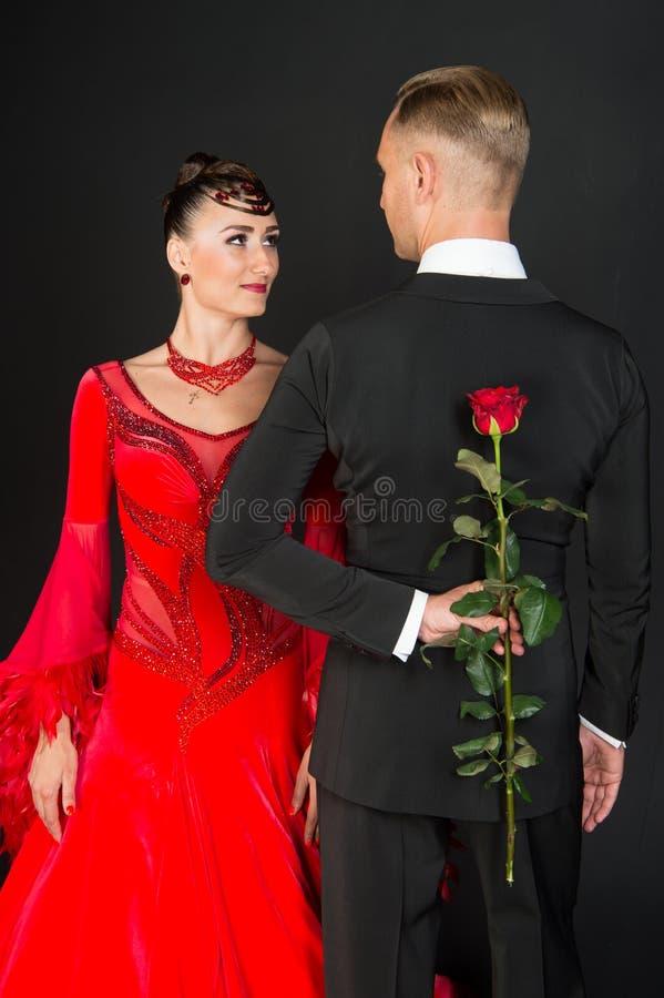 Par av förälskade balsaldansare Sinnlig blomma för kvinna- och manskinnros Kvinna i röd klänning och macho i smoking red steg arkivfoton