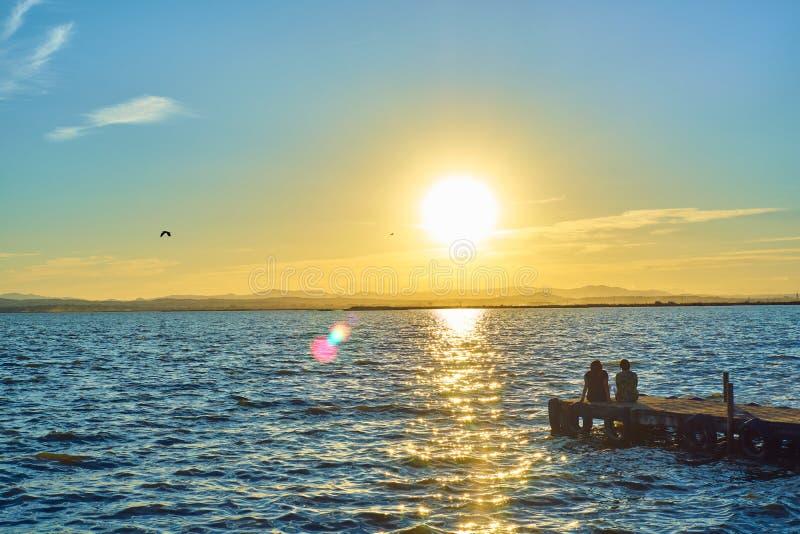 Par av flickor beskådar solnedgången som sitter på skeppsdockan av Albuferaen i Valencia arkivbilder