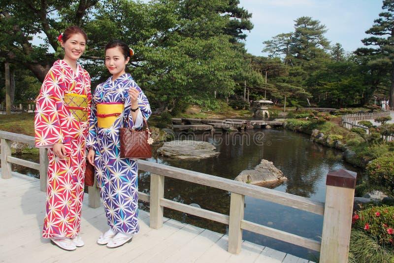 Par av flickor som bär den färgrika traditionella japanska kimonot i Kenrokuen, den berömda japanska landskapträdgården i Kanazaw