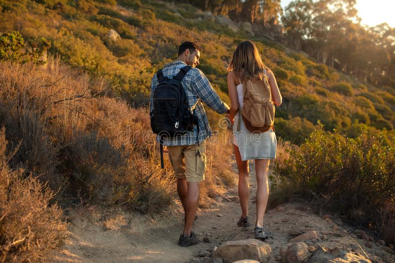 Par av fotvandrare som går ner kullen Man och kvinna med ryggsäcken som går ner bergslingan arkivbilder