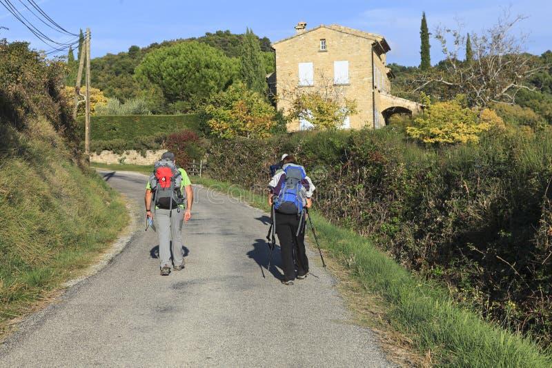 Par av fotvandrare som går på vägen arkivfoton
