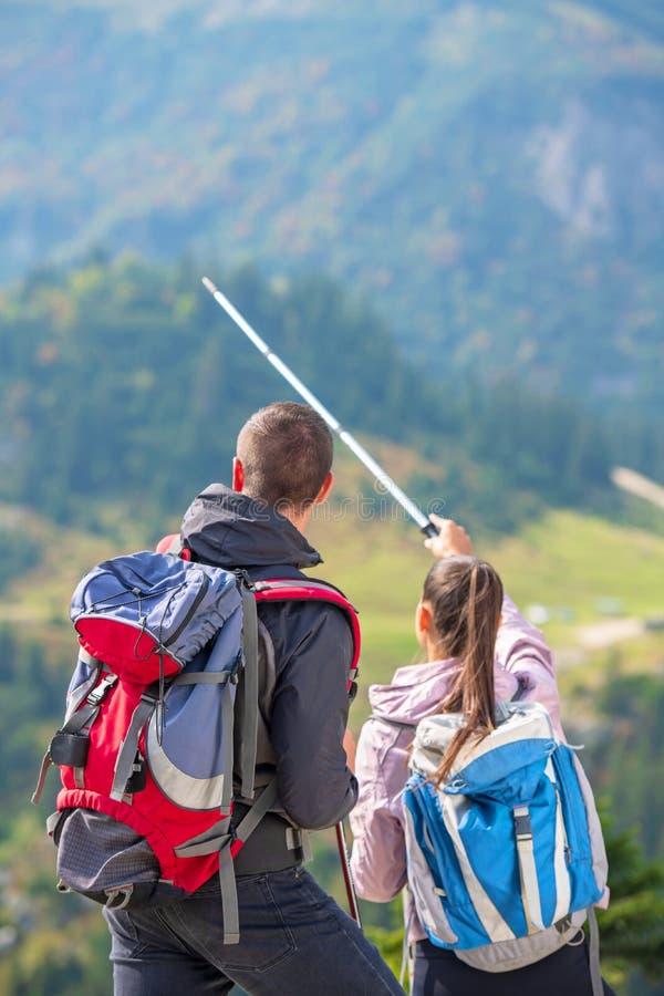 Par av fotvandrare som visar vägen med trekking poler upp på bergmaximumet arkivbilder