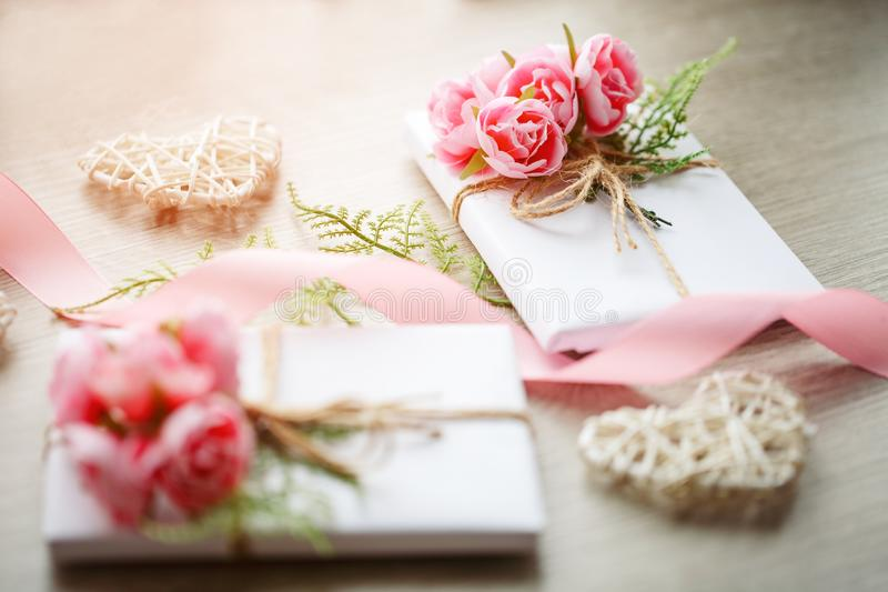 Par av gåvaaskar som slås in med enkelt vitt hantverkpapper och dekoreras med buketten av rosor och den gröna gruppen arkivfoton
