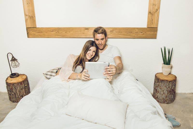 Par av grabben och flickan i säng som håller ögonen på en minnestavla arkivbild