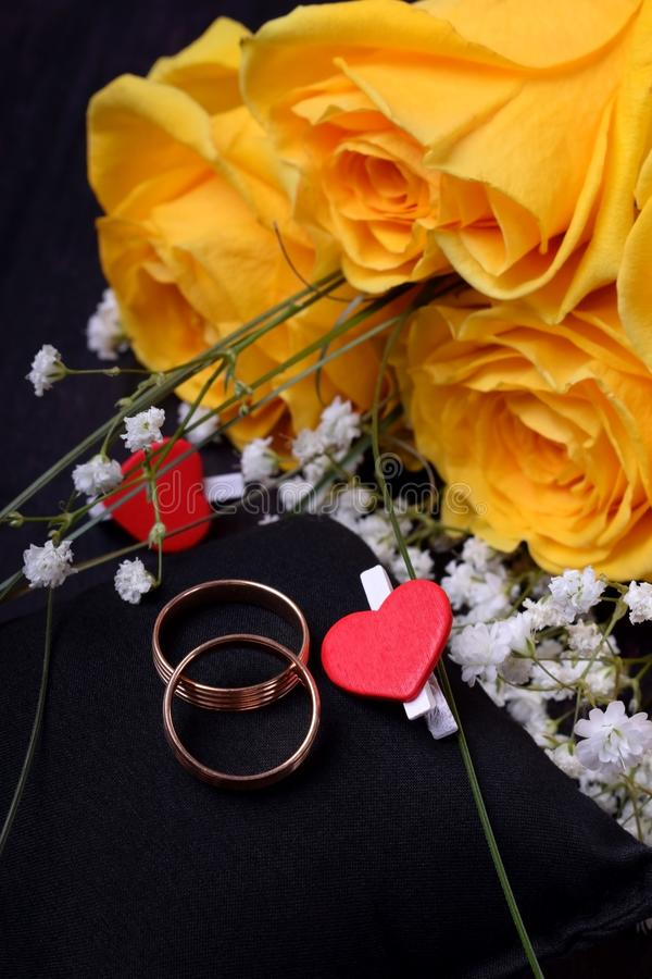 Par av guld- vigselringar och en bukett av rosor fotografering för bildbyråer