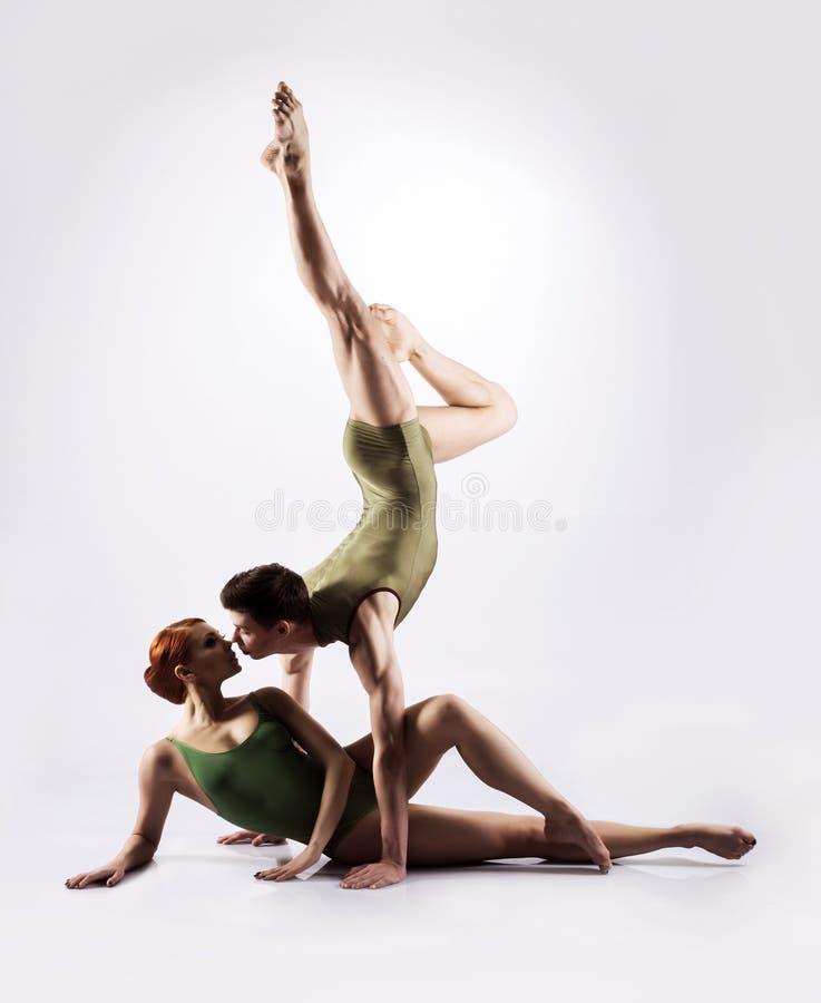 Par av gymnaster som poserar på en ljus bakgrund royaltyfri fotografi
