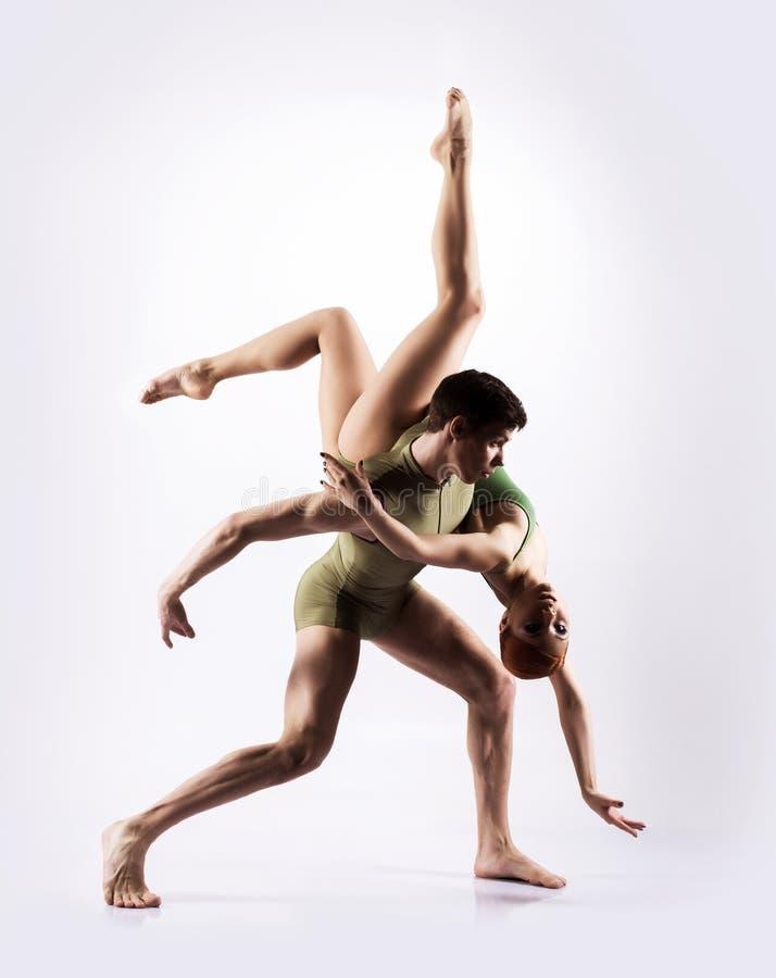 Par av gymnaster som poserar på en ljus bakgrund royaltyfri bild