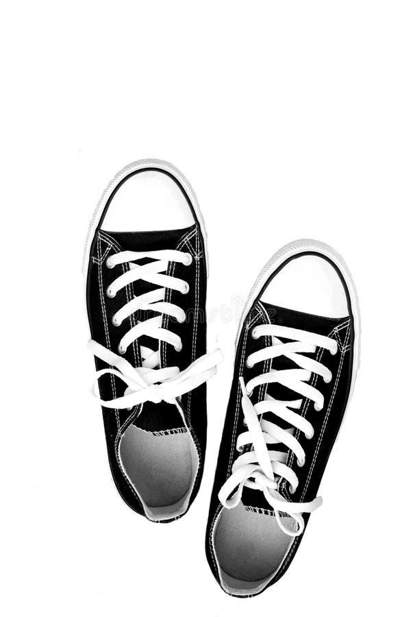 par av gymnastiksko-färgade rinnande skor för ungdom på en vit backgrou arkivfoto