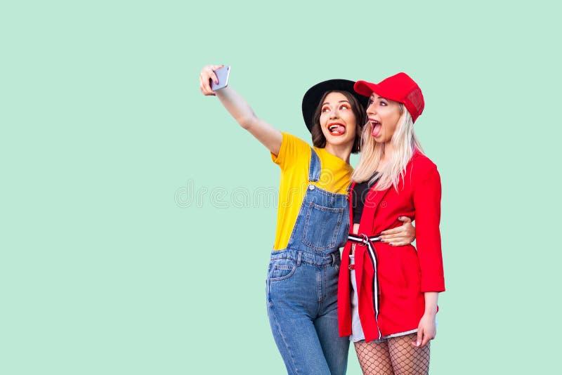 Par av härliga stilyshhipsterbästa vän i trendig kläder som kramar med förälskelse, poserar för kamera och gör selfie eller royaltyfri fotografi