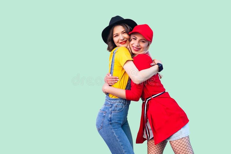 Par av härliga stilyshhipsterbästa vän i trendig kläder som står som kramar med förälskelse som är glad att se sig, arkivfoton