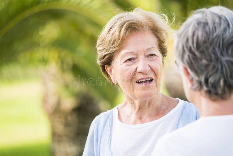 Par av h?ga vuxna v?nkvinnlig talar tillsammans i utomhus- fritidsaktivitet - den pensionerade livsstilen f?r silversamh?lle och fotografering för bildbyråer