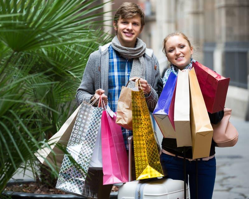 Par av handelsresande med shoppingpåsar royaltyfri foto
