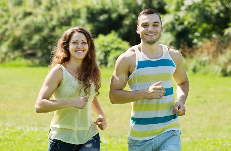 Par av joggers som gör som kör på, parkerar och att le royaltyfri fotografi