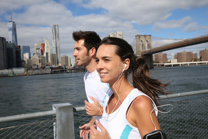 Par av joggers som kör förbi floden i staden arkivbild