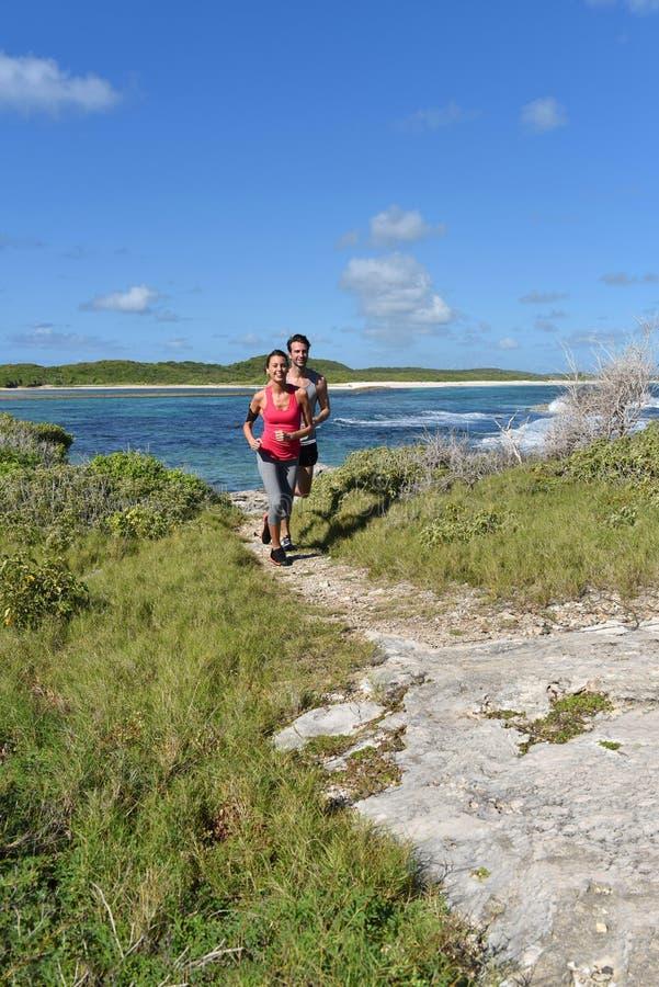 Par av joggers som kör förbi sjösidan arkivbilder