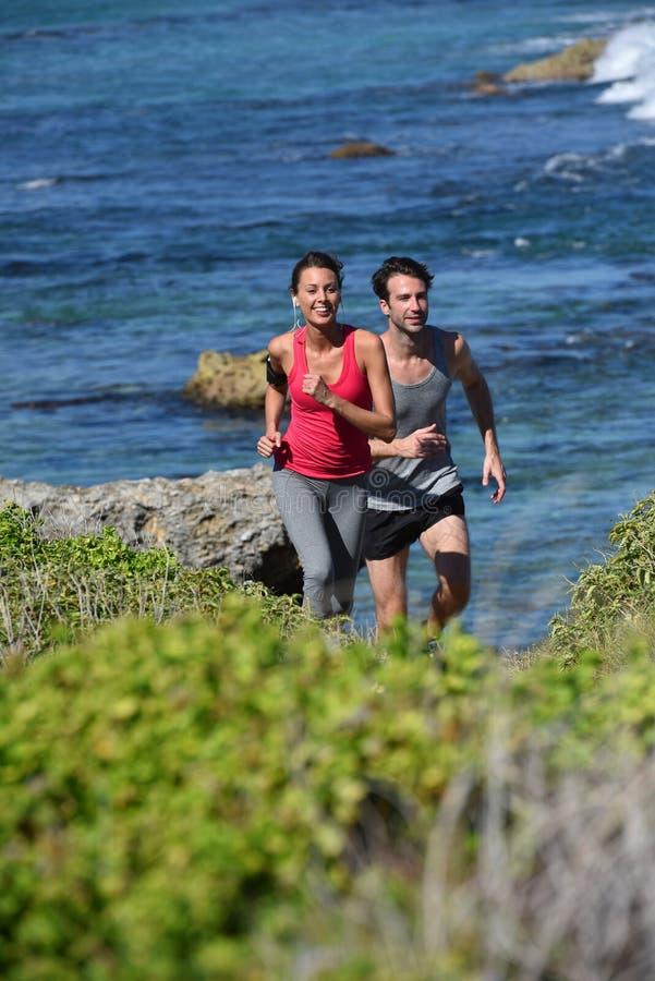 Par av joggers som kör förbi sjösidan royaltyfri foto