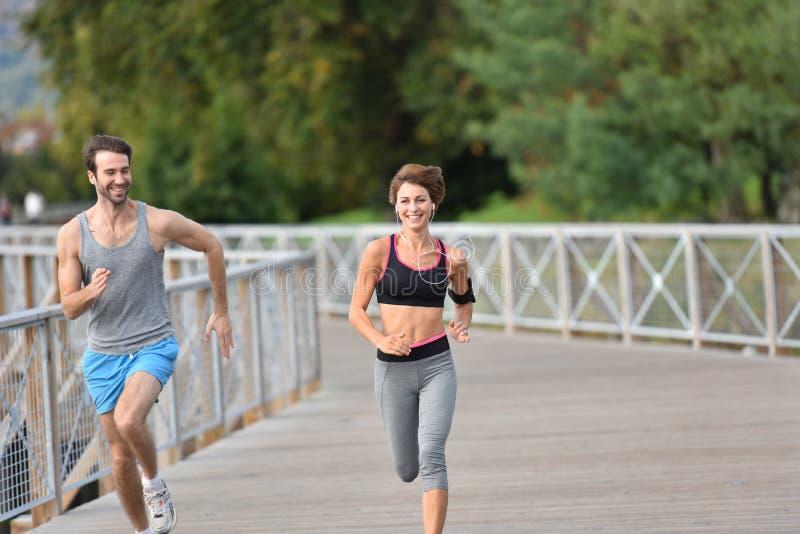 Par av joggers som kör på bron royaltyfria foton