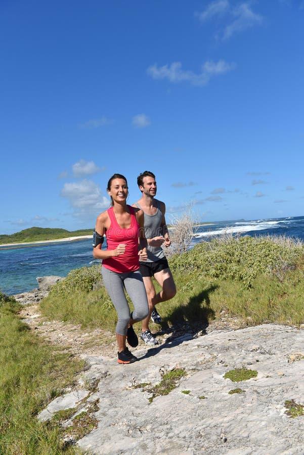 Par av joggers som kör på kustlinjen royaltyfria foton