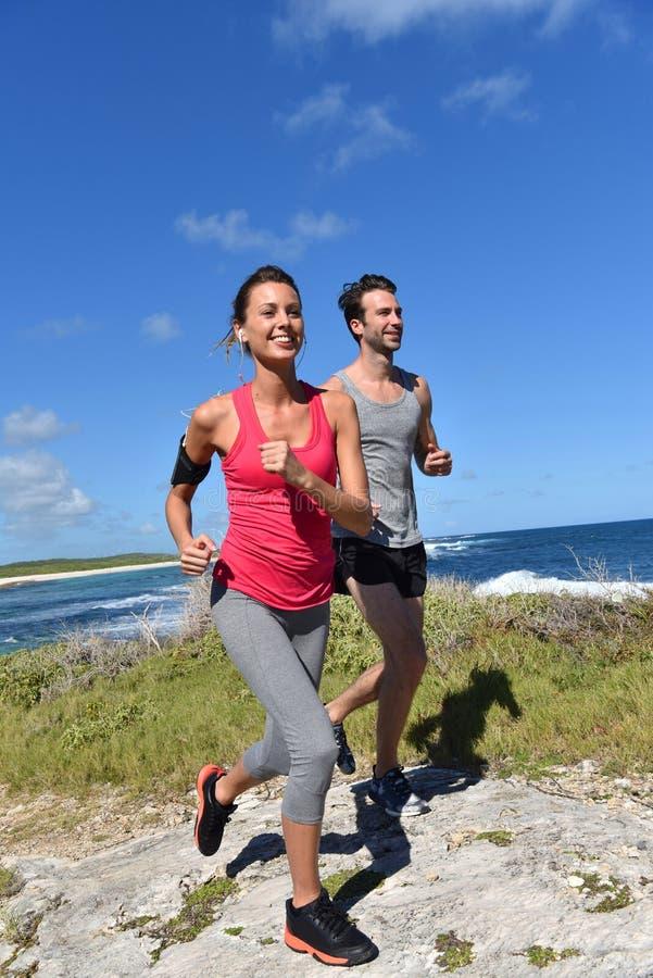 Par av joggers som kör på kustlinjen royaltyfri bild