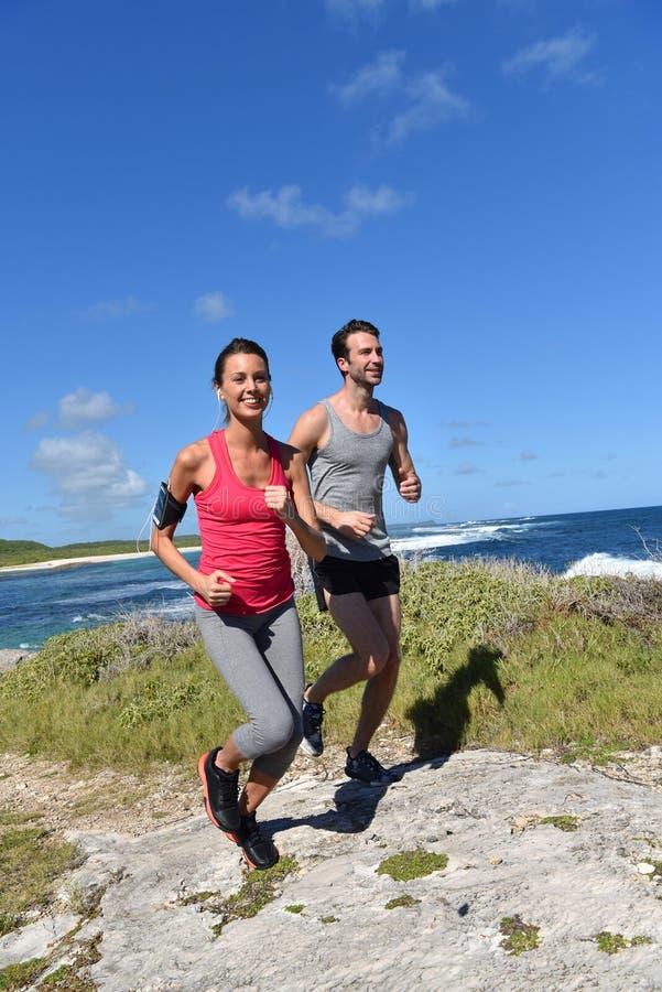 Par av joggers som kör på sjösidan royaltyfri foto