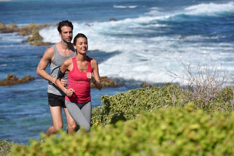 Par av joggers som kör på sjösidan royaltyfria foton