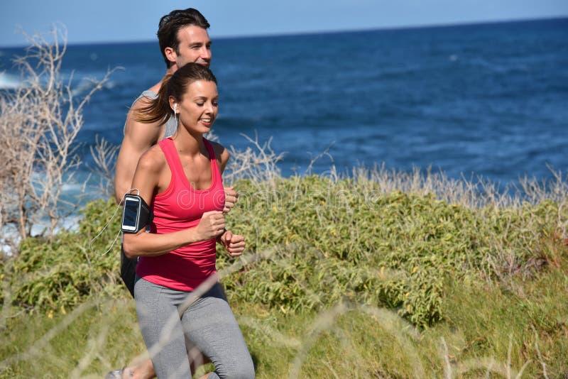 Par av joggers vid sjösidan royaltyfria bilder