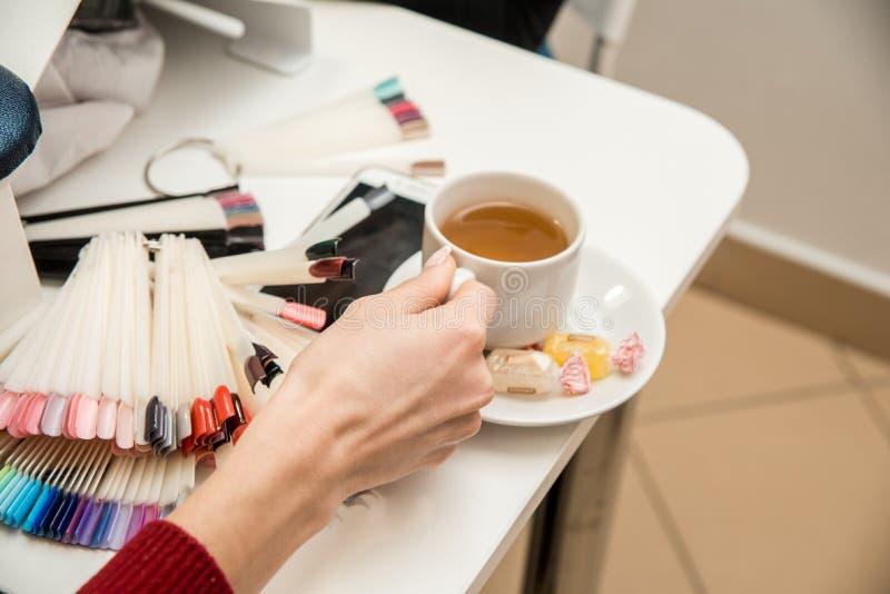 Par av kvinnaklienter som får manikyr i modernt, spikar salongen royaltyfri foto