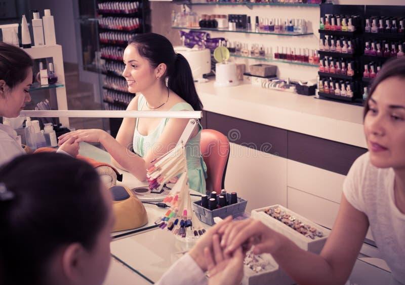 Par av kvinnaklienter som får manikyr spikar in, salongen royaltyfri foto