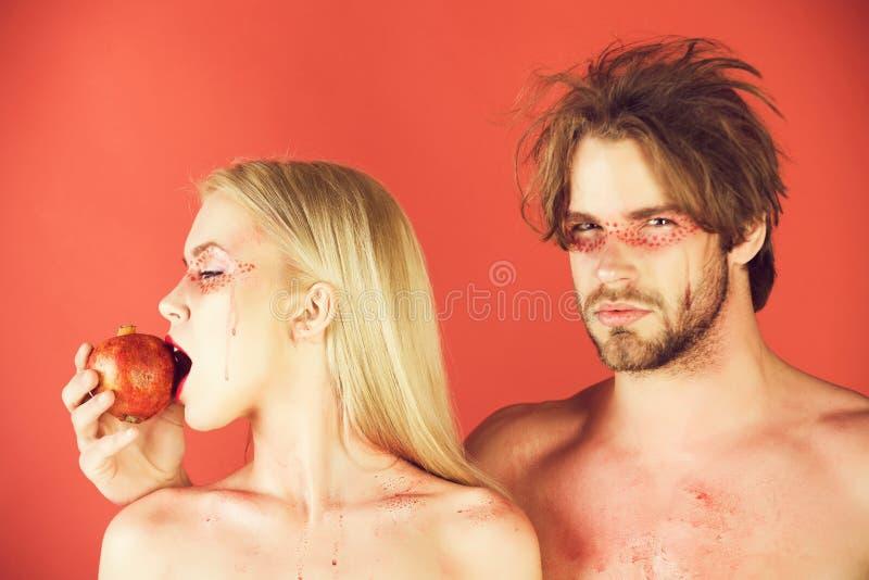 Par av kvinnan och mannen med makeuphållgranatäpplet royaltyfri bild