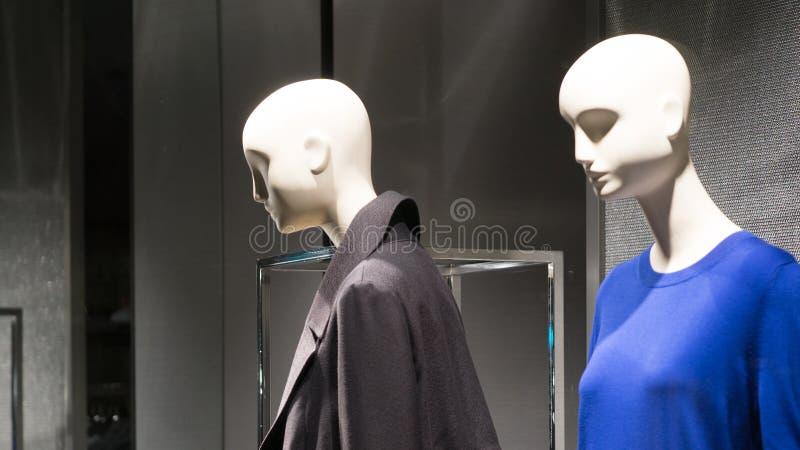 Par av kvinnliga skyltdockor i ett lagerfönster som bär mörk kläder tv? kvinnor arkivfoto
