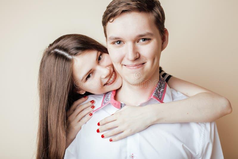 Par av lyckliga le tonåringstudenter, värme färger som har en kyss, livsstilfolkbegrepp royaltyfri foto