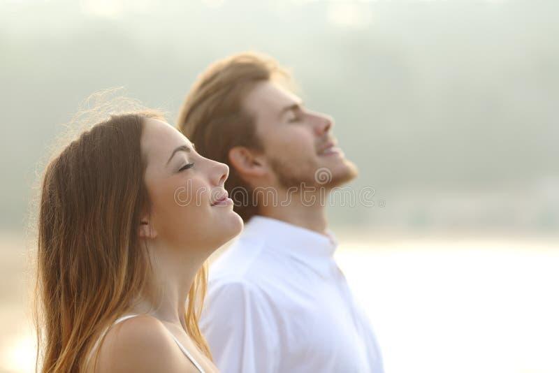 Par av mannen och kvinnan som andas djup ny luft arkivbild