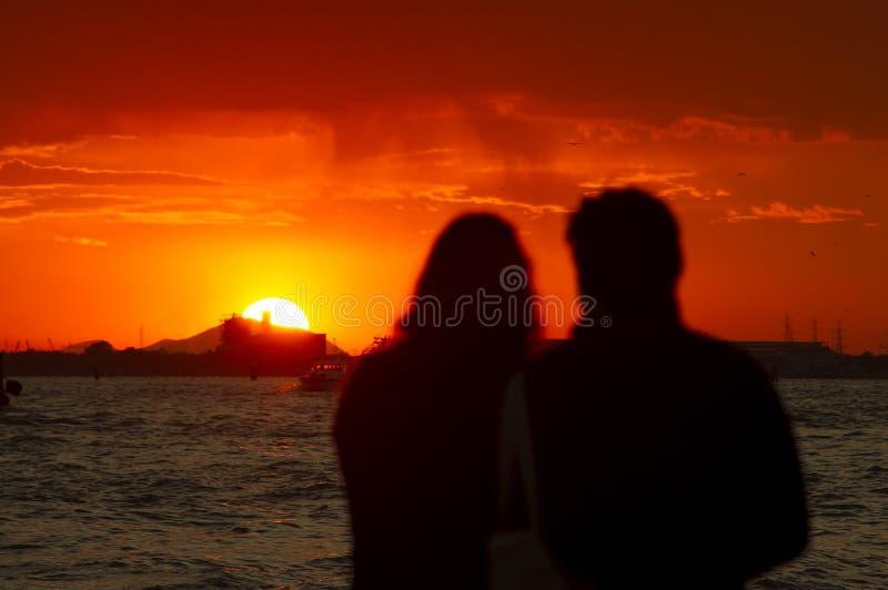 Par av mannen och kvinnan som håller ögonen på härlig solnedgång fotografering för bildbyråer