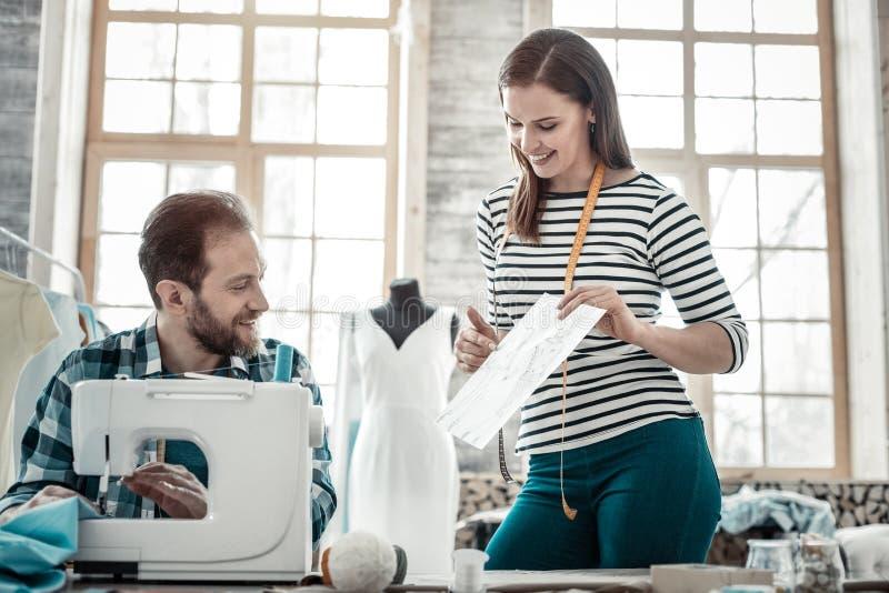 Par av modeformgivare som arbetar i deras lilla atelier royaltyfri bild