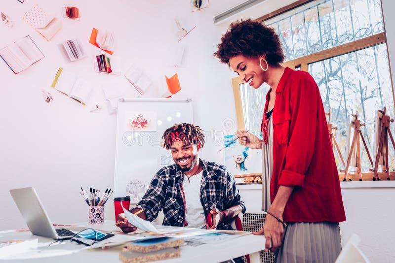 Par av modeformgivare som känner sig upphetsade, medan förbereda sig för show fotografering för bildbyråer