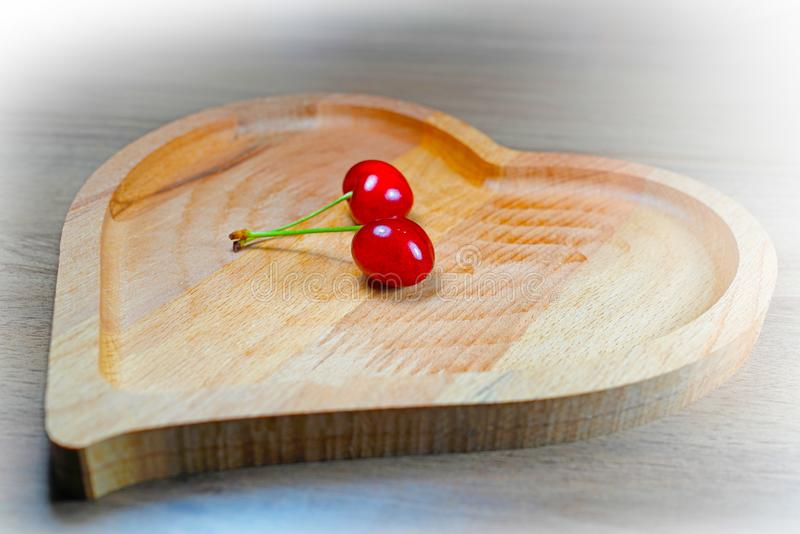 Par av mogna bär för söt körsbär i hjärta-formad träbunke royaltyfria foton
