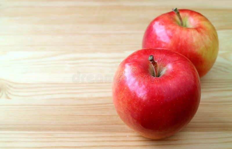 Par av nya mogna röda äpplen som isoleras på den naturliga trätabellen med kopieringsutrymme fotografering för bildbyråer