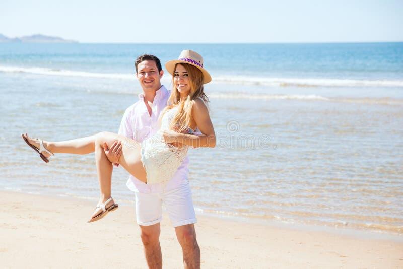 Par av nygifta personer på stranden arkivbild
