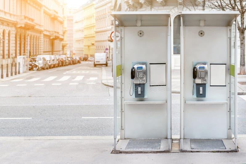 Par av payphonebåset i Wien mittgata Två moderna offentliga telefoner på den europeiska stadsgatan Copyspace royaltyfri foto