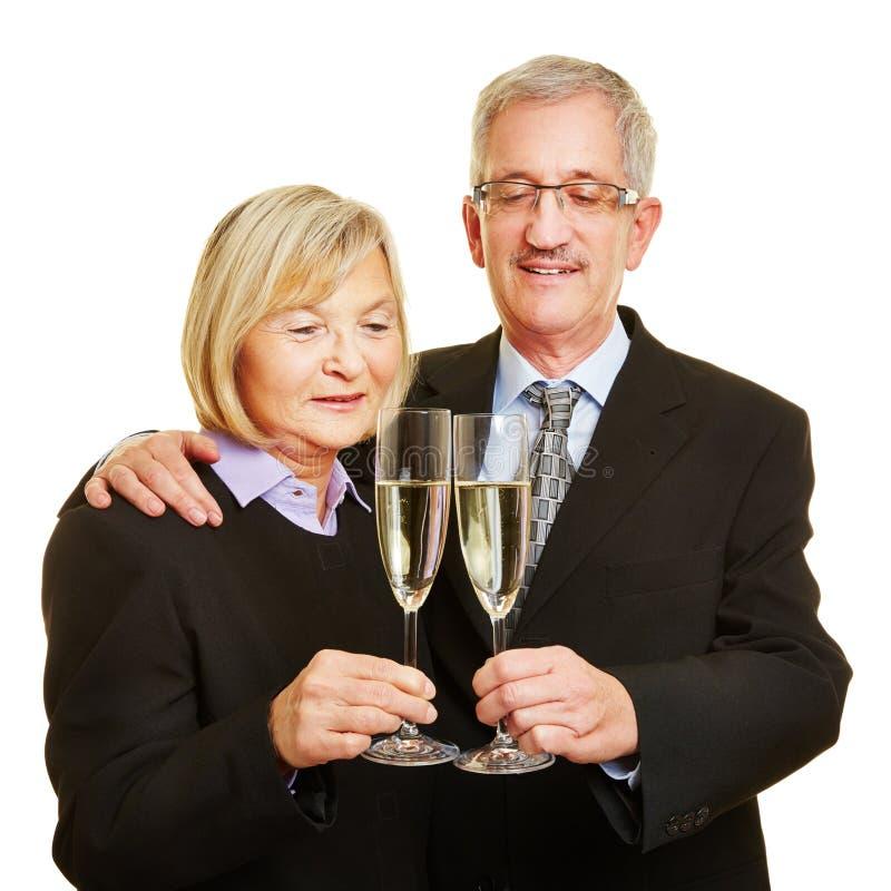 Par av pensionärer startar av med exponeringsglas av mousserande vin arkivfoto