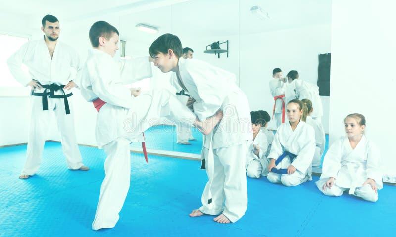 Par av praktiserande nya karateflyttningar för pojkar arkivfoto