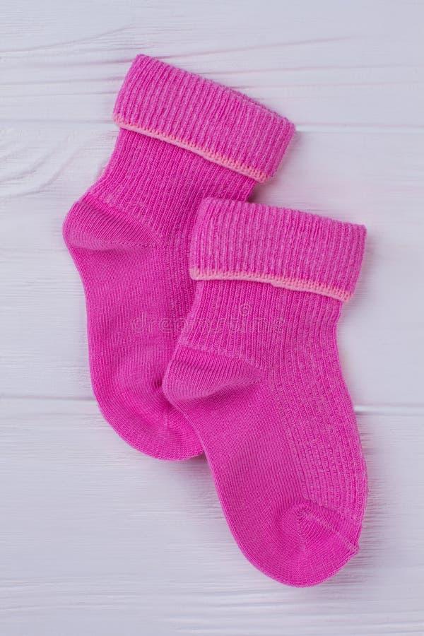 Par av rosa ull övervintrar sockor för nyfött behandla som ett barn royaltyfri foto