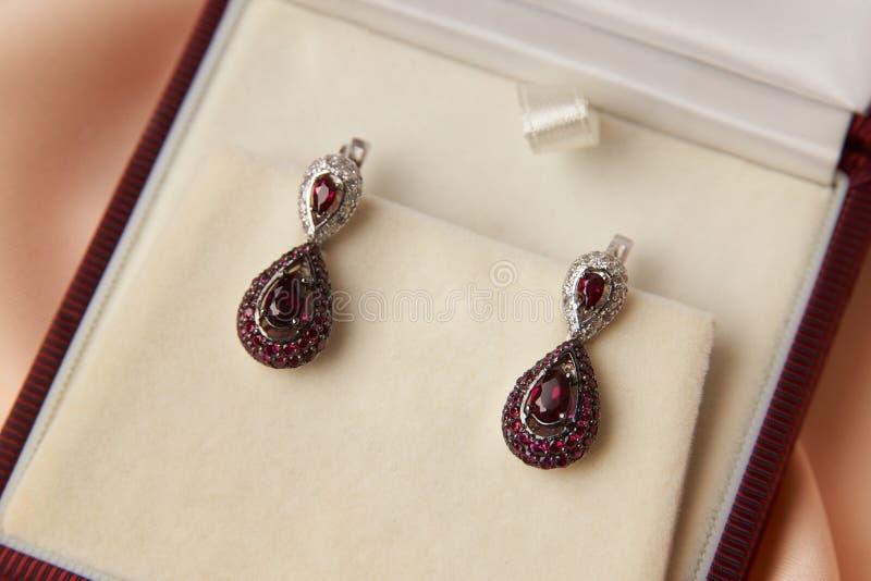 Par av rubindiamantörhängen i smyckenask royaltyfri foto