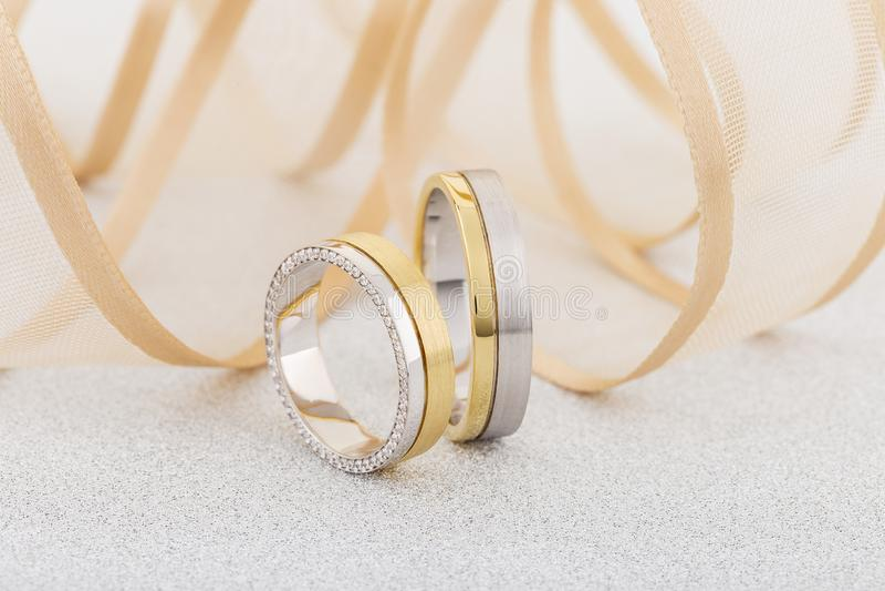 Par av silver och guld- kombinerade cirklar med bandet p? bakgrund royaltyfri bild