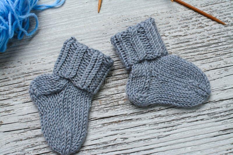 Par av små woolen sockor för nyfött på trätappningtabellen royaltyfri bild