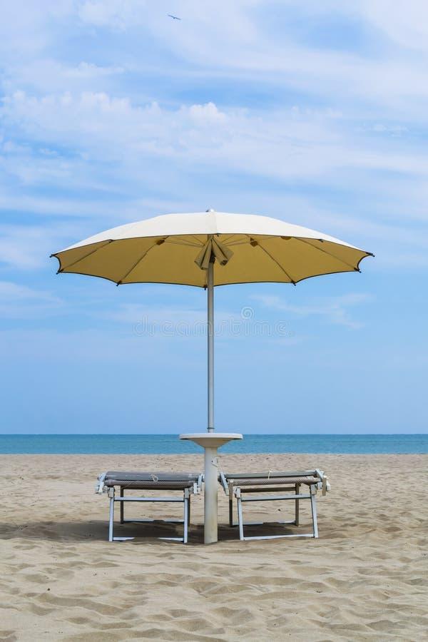 Par av soldagdrivare och ett strandparaply p? en ?de strand Semester- och fritidbegrepp arkivfoto