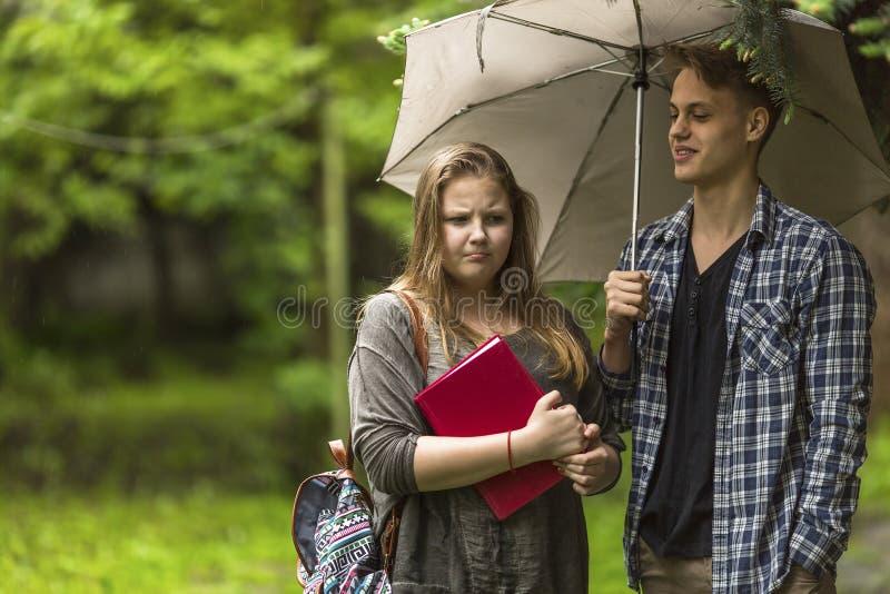 Par av studentflickan med en bok och grabben med paraplyet utomhus royaltyfria bilder