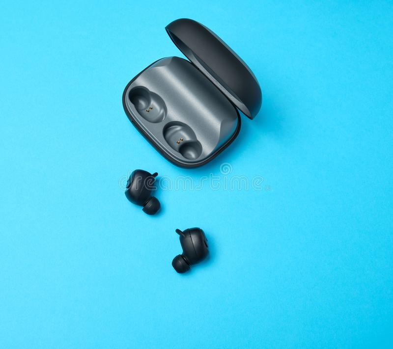 par av svart trådlös liten hörlurar och en laddande ask arkivbild