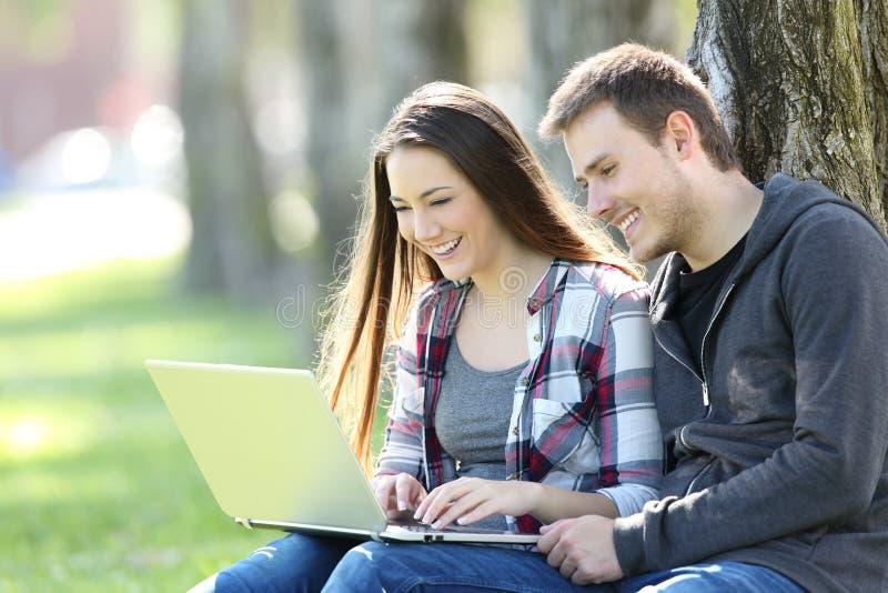Par av tonår som håller ögonen på på linjen innehåll royaltyfria bilder